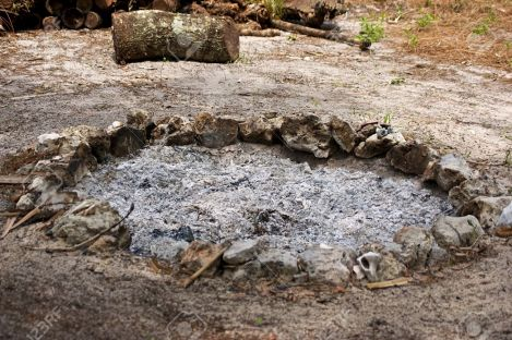 17102924-A-round-fire-pit-made-up-of-stones-and-seashells-is-filled-with-ash-from-a-burnt-out-fire-there-is-f-Stock-Photo